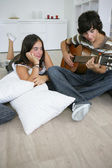 Teenage brunette lost in admiration for boyfriend playing guitar — Stock Photo