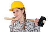 Woman holding sledge-hammer over shoulder — Stock Photo