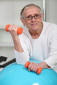 Elderly woman lifting weights in gym — Stock Photo