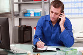 Plumber taking a call in an office and making an appointment in his diary — Foto de Stock
