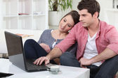 Couple relaxing at home in front of their laptop — Stock Photo