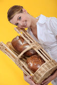 Female baker holding bread in a basket — Stock Photo