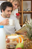 Couple reading the newspaper over breakfast — Stock Photo