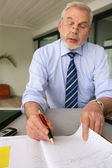 Senior businessman filling in diary — Stock Photo