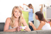 Two female friends playing video games with other friend in background — Stock Photo