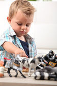 Young boy playing with a selection of toy figurines and animals — Stok fotoğraf