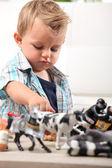 Genç çocuk oyuncak figürler ve hayvanların bir seçim ile oynama — Stok fotoğraf