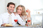 Couple sat at table with wine — Stock Photo