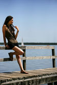 Contemplative brunette stood on jetty — Stock Photo