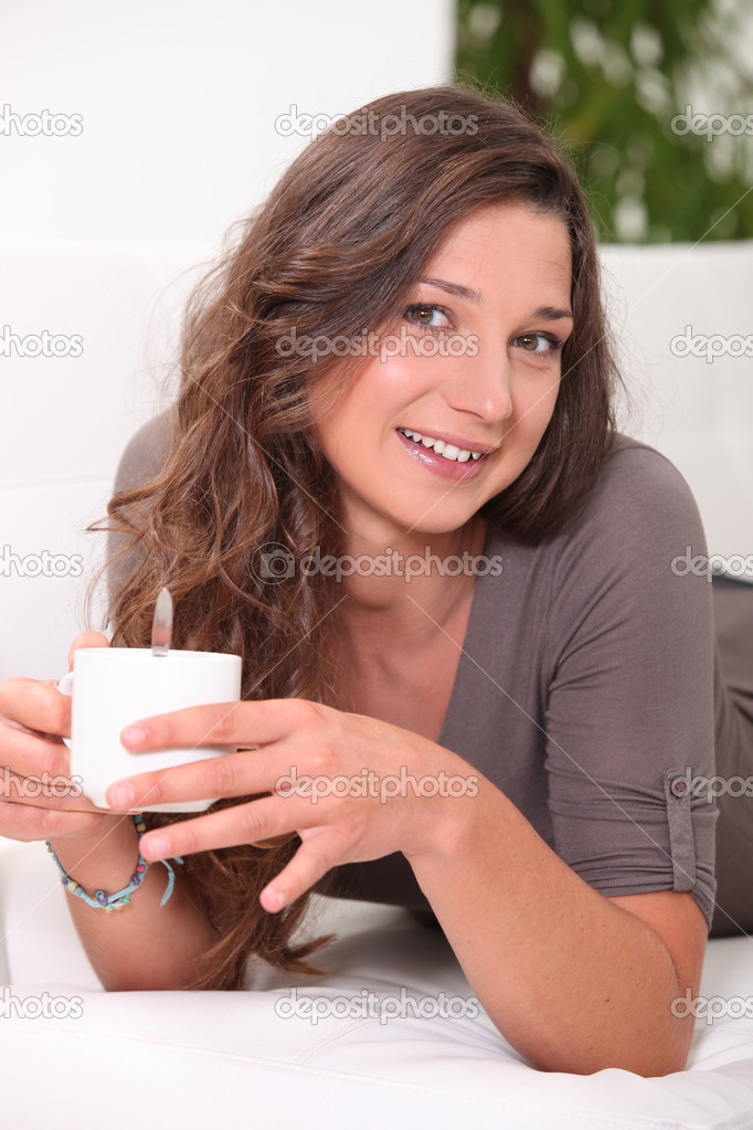 Young woman having a hot drink at home  Stock Photo #8962502