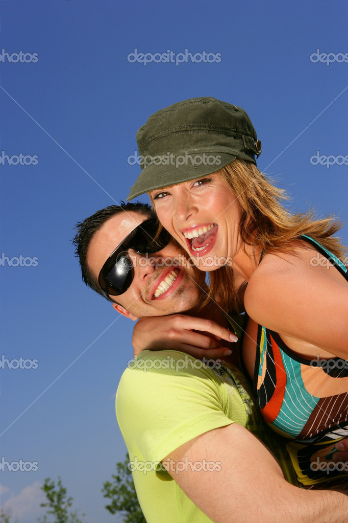 Young couple laughing against a blue sky — Foto Stock #8966125