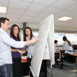 Office team looking a growth chart on a whiteboard — Stock Photo #8970328