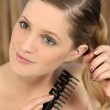 Pretty young woman untangling her hair — Stock Photo