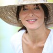 30 years old brunette wearing a straw hat and a summer dress — Stock Photo