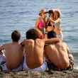 Lads watching a group of girls in the sea — Stock Photo