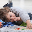 Child lying on the floor playing with a puzzle — Stock Photo