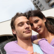 Stock Photo: Smiling couple outside block of flats