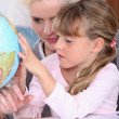 Womand child looking at globe — Stockfoto #8971052