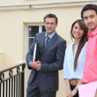 Couple standing outside a house with an estate agent — Stock Photo