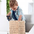 Little boy tidying up his toys in basket — Stock Photo #8971502