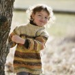 Young girl playing amongst the trees — Stock Photo
