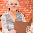 Woman reading a menu in a restaurant — Stock Photo