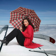 Brunette sat on the wing of an airplane - Stock Photo