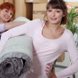Young women carrying a rolled-up rug on moving day — Stock Photo #8972025