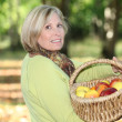 Mature blonde woman in orchard - Stock Photo