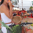Summery woman eating an apricot at a market stall — Stock Photo