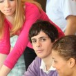Young man surrounded by his peers — Stock Photo #8972177