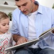 Stock Photo: Father reading to his daughter