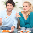 Young couple dining in front of TV — Stock Photo