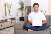 Man using a laptop computer in his front room — Stock Photo