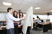 Office team looking a growth chart on a whiteboard — Stock Photo