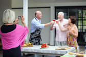 Older woman taking a photo at a party — Stock Photo