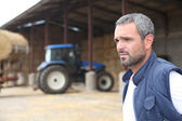 Farmer standing in front of a barn containing a tractor — Stock Photo