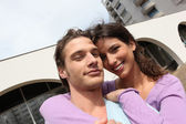 Smiling couple outside a block of flats — Stock Photo