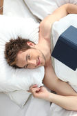 Man in bed reading book — Stock Photo