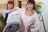 Young women carrying a rolled-up rug on moving day — Stock Photo