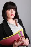 Brunette holding colourful folders — Stock Photo
