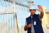 Worker on a construction site waving his hand — Stock Photo