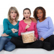 Three friends watching television and eating popcorn — Stock Photo