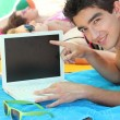 A young man on the beach showing a computer — Stock Photo #9038956
