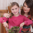 Stock Photo: Mother and daughter making salad