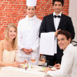 Stock Photo: A couple being served by a waiter and a chef in a restaurant