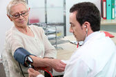 Older woman having her blood pressure taken — Stock Photo