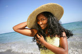 Woman in straw hat having fut at the beach — Stock Photo