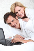 Happy couple on laptop in dressing gown. — Stock Photo