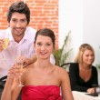 Couple holding champagne flutes in restaurant — Stock Photo #9040761